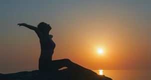 Girl practices yoga near the ocean. During sunrise time Royalty Free Stock Photography