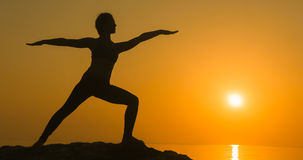Girl practices yoga near the ocean Stock Images