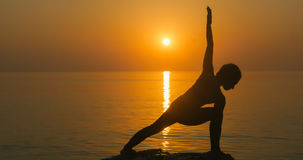Girl practices yoga near the ocean. During sunrise time. Warrior pose Royalty Free Stock Images