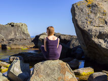 Girl practices yoga near the sea, on the rock, slow motion hd video. Woman practices yoga near the sea, on the rock, slow motion hd video stock photos