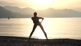 A girl practices yoga on the seashore in the morning at sunrise in slow motion. A slender young girl in a swimsuit practices yoga on the seashore in the morning stock video