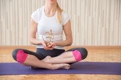 A girl practices yoga and sits in a lotus position with the sign of mantra om. A girl practices yoga in a gym and sits in a lotus position with the sign of stock image