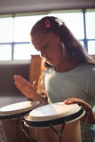 Girl practicing bongo drums in classroom royalty free stock photography