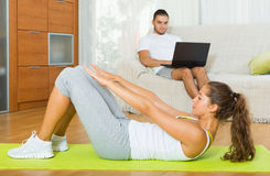 Girl practicing fitness and boyfriend resting Stock Photography
