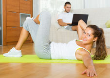 Girl practicing fitness and boyfriend  resting on couch Royalty Free Stock Photo