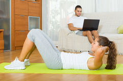 Girl practicing fitness and boyfriend resting. With laptop resting on sofa Royalty Free Stock Photos