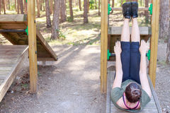 Girl practicing fitness. Girl doing some Abdominal ABS Exercises through a wooden structure inside a pine forest. Copy space on the left royalty free stock photo