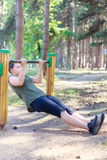 Girl practicing fitness. Girl doing some pull-ups inside a pine forest through a wooden structure stock photo