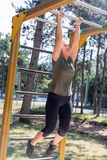Girl practicing fitness. During the midday, girl doing gymnastic exercises on a wooden structure made for practicing different type of exercise. She is inside an royalty free stock photos