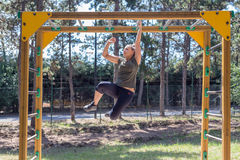 Girl practicing fitness. During the midday, girl doing gymnastic exercises on a wooden structure made for practicing different type of exercise. She is inside an royalty free stock images
