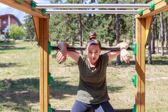 Girl practicing fitness. During the midday, girl doing gymnastic exercises on a wooden structure made for practicing different type of exercise. She is inside an stock image