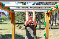 Girl practicing fitness. During the midday, girl doing gymnastic exercises on a wooden structure made for practicing different type of exercise. She is inside an royalty free stock photo