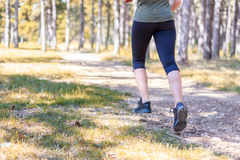 Girl practicing fitness. Girl is running inside an evergreen pine forest royalty free stock photography