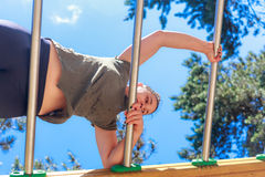 Girl practicing fitness. Under a blue sky, girl doing gymnastic exercises on a wooden structure made for practicing different type of exercise. she is surrounded stock images