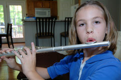 Girl practicing flute at home Royalty Free Stock Photos