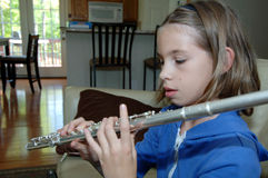 Girl practicing flute at home. A girl practicing her flute at home Stock Photography