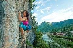 Girl practicing free climbing on rock with panorama of the villa. Ge stock images
