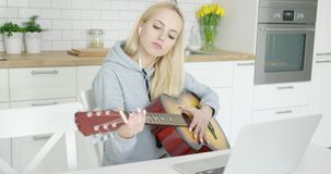 Girl practicing guitar and using laptop stock footage
