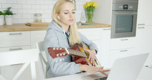 Girl practicing guitar and using laptop Royalty Free Stock Photo