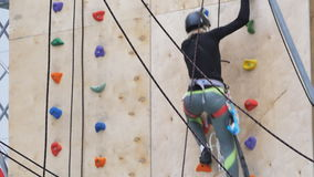 Girl practicing on the wall for rock climbing stock video footage