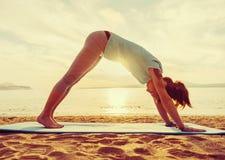 Girl practicing yoga on beach stock photo