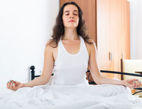 Girl practicing yoga in bed Stock Photography