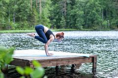 Girl practicing yoga, doing Bakasana exercise, Crane pose,  on the lake.   Concept of healthy life and natural balance