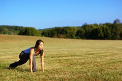 Girl Practicing Yoga In Field. Girl practicing yoga in a summer meadow stock photography