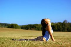 Girl Practicing Yoga In Field. Girl practicing yoga in a summer meadow royalty free stock photo