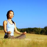 Girl Practicing Yoga In Field. Girl practicing yoga in a summer meadow stock image