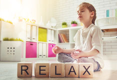 Girl is practicing yoga. Little child girl playing with blocks and having fun. Blocks have letters. Child arranges cubes and word Relax. Girl is practicing yoga Stock Photo