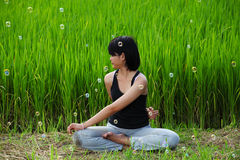 Girl practicing yoga in paddy field Stock Photo
