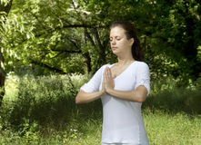 Girl practicing yoga. In the park Stock Photography