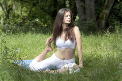 Girl practicing yoga in the park. Young woman doing yoga exercise outdoor Royalty Free Stock Image
