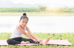 Girl practicing yoga pose on a mat in park Stock Image