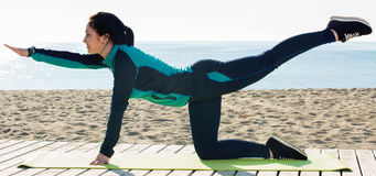 Girl practicing yoga poses on beach by sea at daytime Stock Photo