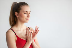 Girl practicing yoga showing love gesture. Young beautiful athletic girl practicing yoga and holding arms in heart gesture on grey background with copy space Stock Photo