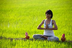 Girl practicing yoga,sitting with lotus flower Stock Photos