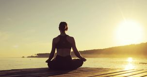 Young woman is meditating in Lotus Pose sitting on pier near the sea at sunset. stock footage