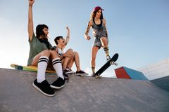 Girl practising skateboarding with friends cheering royalty free stock image