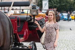 Girl in Prague and Chariot. Girl in the streets of Prague posing in front of a tourist chariot, Czech Republic, Europe Stock Images