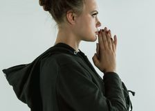 Young beautiful pensive girl in black clothes praying hopefully, over white background. Girl pray, address a solemn request or expression of thanks to a deity or stock image