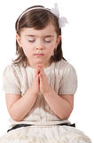Girl Praying. Portrait of young adorable girl praying isolated on white royalty free stock image
