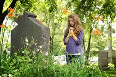 Girl praying at the cemetery Stock Image