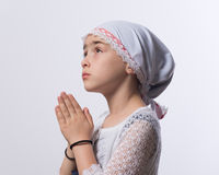 Girl Praying. A closeup of a 8 year old girl with head cover praying stock images