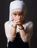 Girl Praying. A closeup of a 8 year old girl with head cover praying stock photos