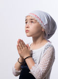 Girl Praying. A closeup of a 8 year old girl with head cover praying royalty free stock photo