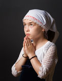 Girl Praying. A closeup of a 8 year old girl with head cover praying stock image