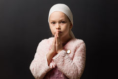 Girl Praying. A closeup of a 7 year old girl with a headscarf praying royalty free stock image