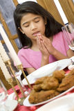 Girl praying during dinner Stock Photo